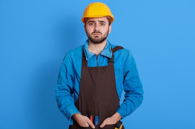 Helpless bearded engineer wearing yellow protective helmet keeping hands in pockets of apron, looks sad and upset, does not know what to do