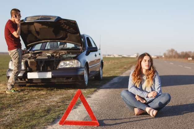 Helpless couple stop on road as have breakdown of car. desperate male calls somebody via cell phone
