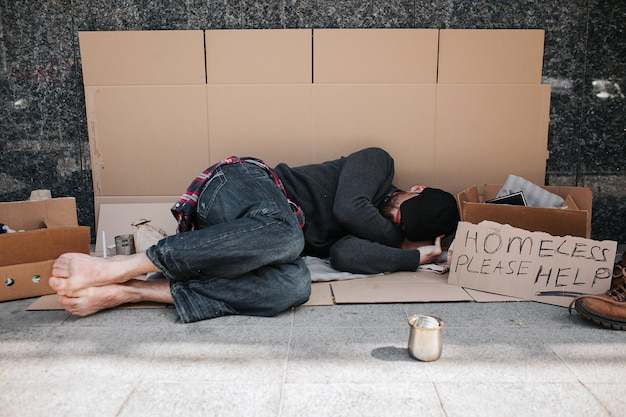 Helpless and defenceless man is lying on the cardboard on concrete floor and sleeping