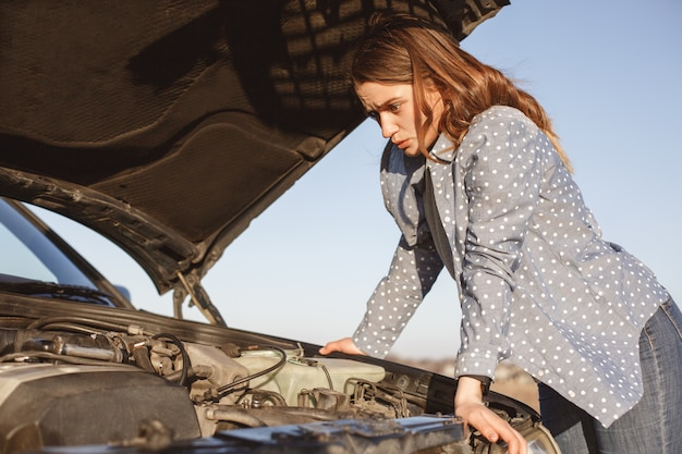 Helpless female looks desperately at opened car hood, has breakdown on road, can`t solve problem, has shocked expression