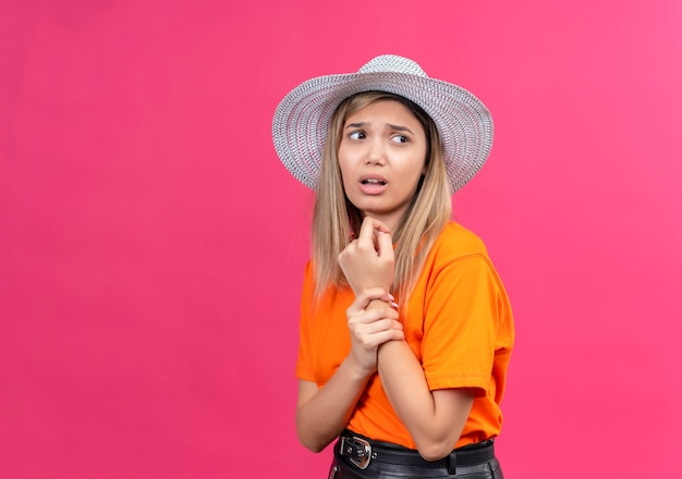 A helpless pretty young woman in an orange t-shirt wearing sunhat holding her painful wrist while looking side on a pink wall