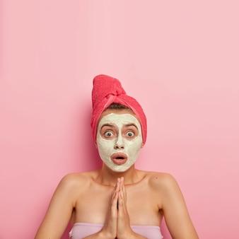La donna indifesa e scioccata tiene i palmi premuti insieme, fissa con il fiato sospeso, chiede consigli su come prendersi cura meglio della carnagione e della pelle, applica una maschera all'argilla naturale sul viso, avvolta in un asciugamano