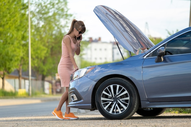 車の近くに立っている無力な女性が、開いたボンネットで道路サービスに助けを求めています。車両に問題を抱えている若い女性ドライバー。