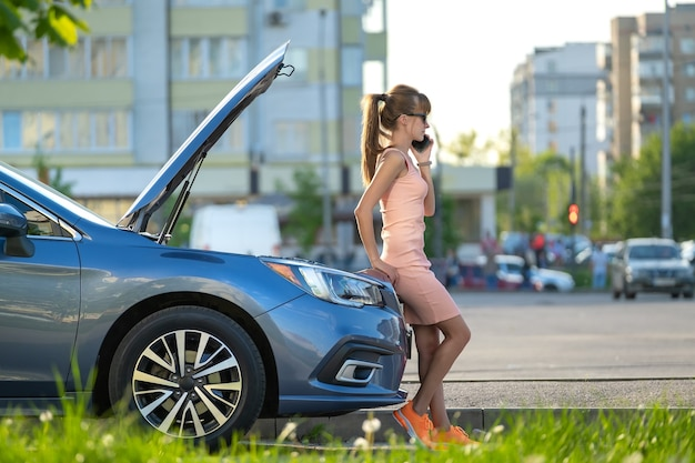 Helpless woman standing near her car with open bonnet calling road service for help. young female driver having trouble with vehicle.