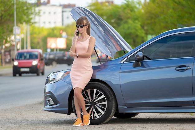 Беспомощная женщина, стоящая возле своей машины с открытым капотом, взявшись за мобильный телефон, звонит в дорожную службу за помощью. молодая женщина-водитель, имеющая проблемы с автомобилем.