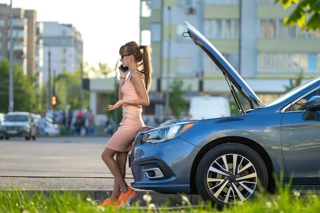 도움을 요청하는 도로 서비스에 전화를 걸고 후드를 열고 차 근처에 서 있는 무력한 여성. 차량에 문제가 있는 젊은 여성 운전자.