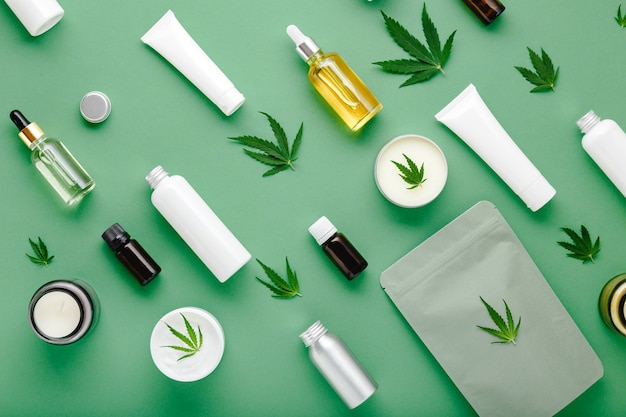 Hemp cbd oil serum in glass dropper bottle with cannabis leaves, moisturizing cream, serum, lotion, essential oil. cannabis leaf with skincare cosmetic product flat lay pattern on green background.