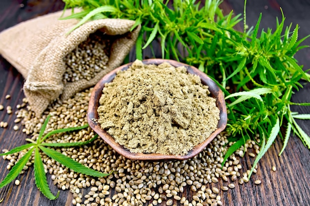 ボウルに麻の粉、テーブルの上の袋に入った穀物、暗い木の板の背景に大麻の葉