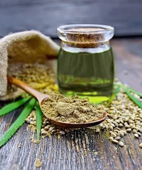 ボウルに麻の粉、テーブルの上の袋に種子、ガラスの瓶に大麻の油、木の板の背景に緑の葉