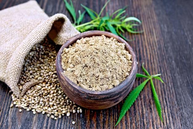 粘土のボウルに麻粉、バッグとテーブルの穀物、木の板の背景に大麻の葉