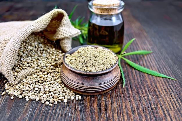 粘土のボウルに麻粉、バッグとテーブルに穀物、ガラスの瓶に油、木の板の背景に大麻の葉と茎