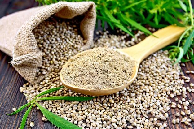 木のスプーンの麻粉、バッグとテーブルの上の穀物、板の背景に大麻の葉と茎