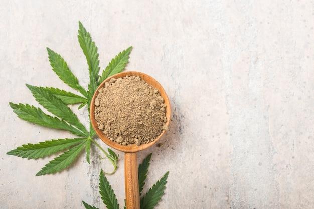 Hemp flour  in wooden spoon .  copy space. cbd cannabis.