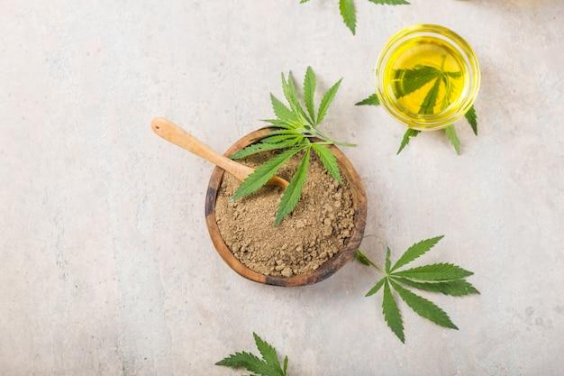 Hemp flour  in wooden spoon and hemp essential oil.  copy space. cbd cannabis.