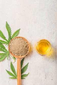 Hemp flour  in wooden spoon and hemp essential oil.  copy space. cbd cannabis.