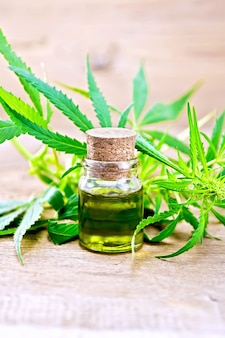 Hemp oil in a glass bottle, leaves and stalks of cannabis on the background of old wooden boards