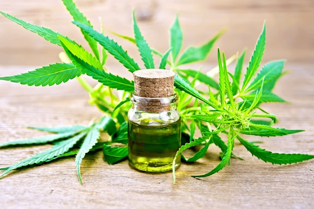 Hemp oil in a glass bottle, leaves and stalks of cannabis on the background of wooden boards