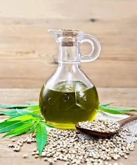 Hemp oil in a glass decanter, grain in a spoon and on the table, cannabis leaves on a wooden board background