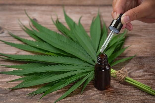 Olio di canapa e foglie di canapa adagiate sul pavimento in legno