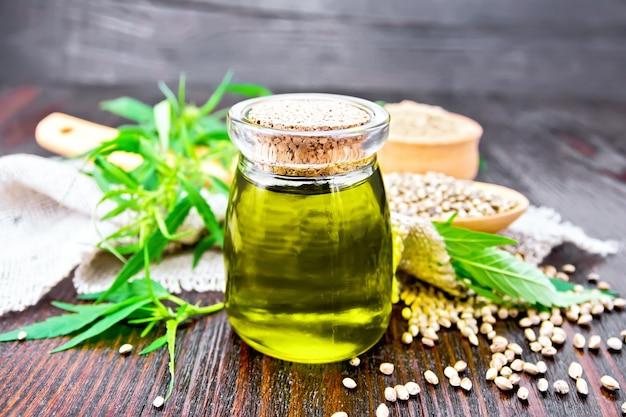 ガラスの瓶にヘンプオイル、スプーンに穀物、ボウルに小麦粉、黄麻布のナプキン、木の板の背景に大麻の葉と茎