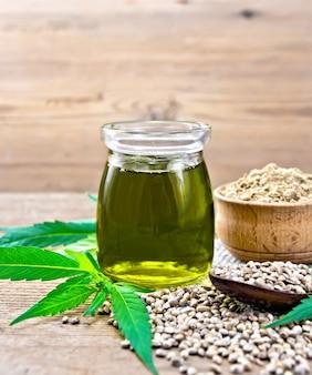 ガラスの瓶に麻油、スプーンに穀物、荒布を着たボウルに小麦粉、古い木の板の背景に大麻の葉