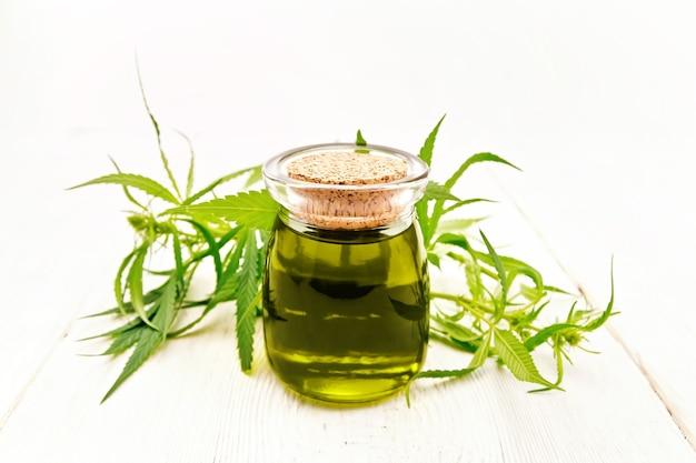 ガラスの瓶の中の麻油、明るい木の板の背景に大麻の葉と茎