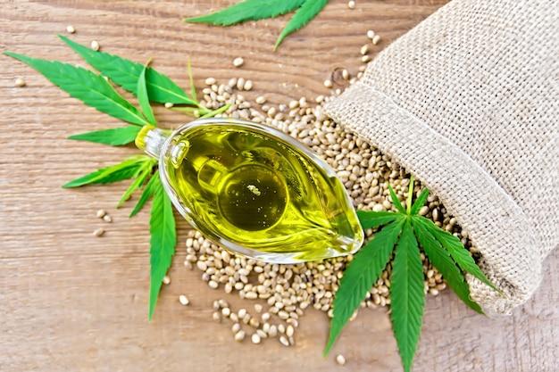 袋に穀物、上から古い木の板を背景に大麻の葉と茎を持つガラスソースボートの麻油