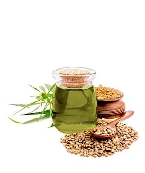 유리 항아리에 대마유, 숟가락과 그릇에 밀가루와 곡물의 더미, 녹색 대마초 잎은 흰색 배경에 고립
