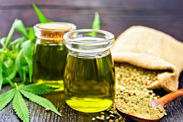 2つのガラス瓶に入った麻油、バッグとテーブルの上にある穀物、スプーンの中の小麦粉、暗い木の板に対して大麻の葉