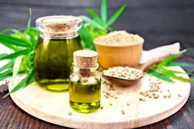 2つのガラス瓶に入った麻油、スプーンの中の穀物、ボウルの中の小麦粉、大麻の葉と茎、暗い木の板の背景に黄麻布のナプキン