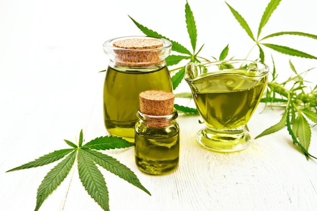 Hemp oil in two glass jars and sauceboat, leaves and stalks of cannabis on the background of light wooden boards