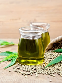 Hemp oil in two glass jars with grain in the bag and on the table, cannabis leaves on the background of wooden boards
