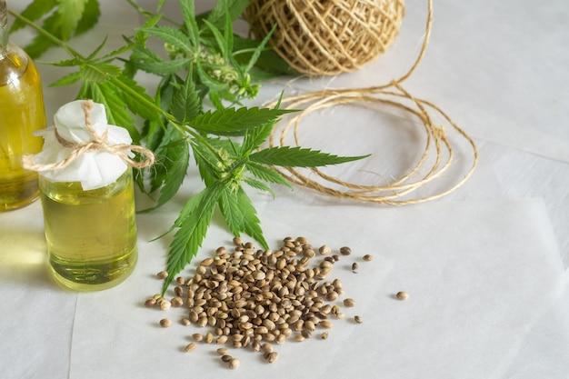 대마 제품 개념입니다. 대마초 기름이 든 병, 실 타래, 흰색 배경에 녹색 식물
