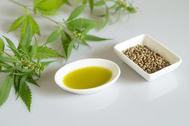 麻製品のコンセプト。大麻種子油と白い背景の上の緑の植物