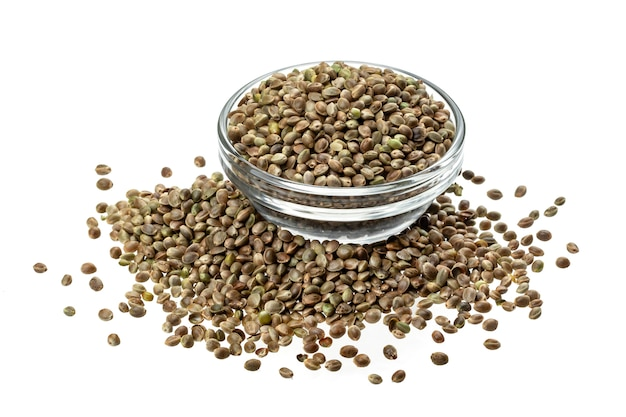 Hemp seeds in bowl isolated on white, close up, macro
