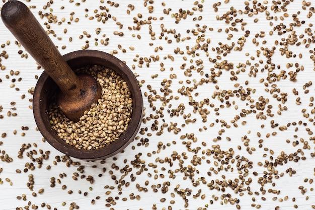 Семена конопли в старой деревянной ступке на белом столе. вид сверху.