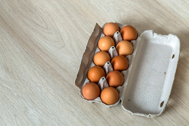 Hen eggs in open cardboard egg carton on kitchen table. healthy organic food and diet concept.