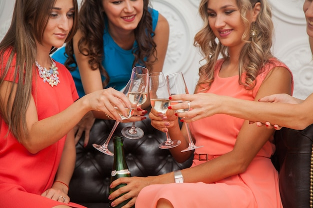 Hen party in cocktail dresses. girls drinking champagne