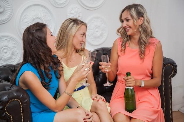 カクテルドレスを着たヘンパーティー。女の子はシャンパンを飲み、心から心を話している