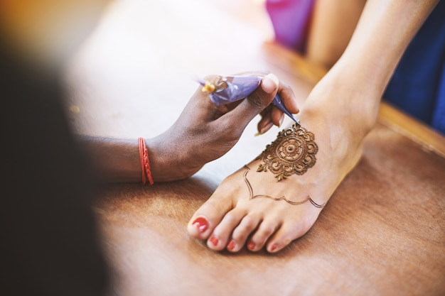 Henna artist (mehndi) painting the foot of women on the indian wedding day