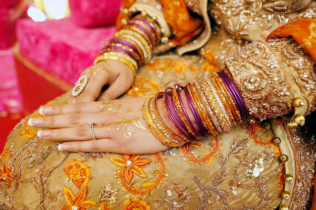 Henna party indian wedding details bride hands with rings bracelets and golden henna close up