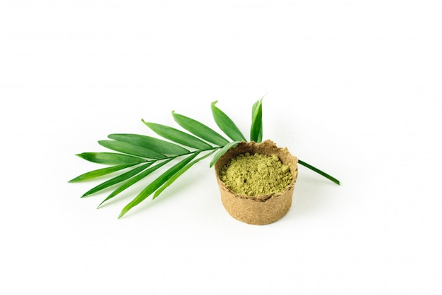 Henna powder for hair and eyebrows with green palm leaf.