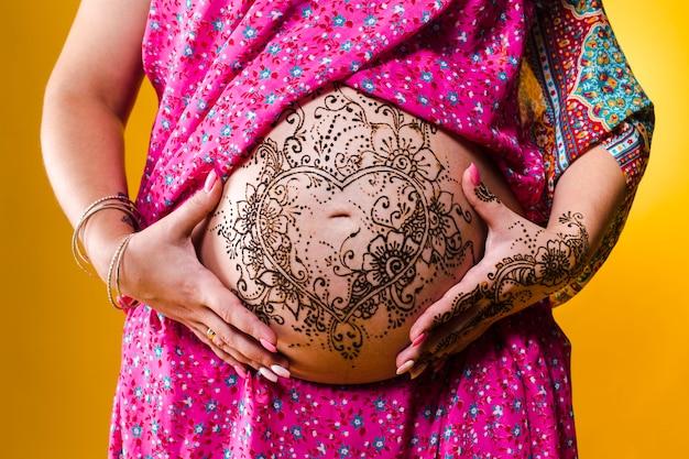 女性の妊娠中の腹にヘナのタトゥー