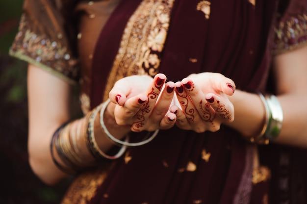 ヘナの結婚式のデザイン、黒い一時的な刺青の入れ墨を持つ女性の手。黒のヘナの入れ墨を持つインドの花嫁の女性の手。ファッション。インド