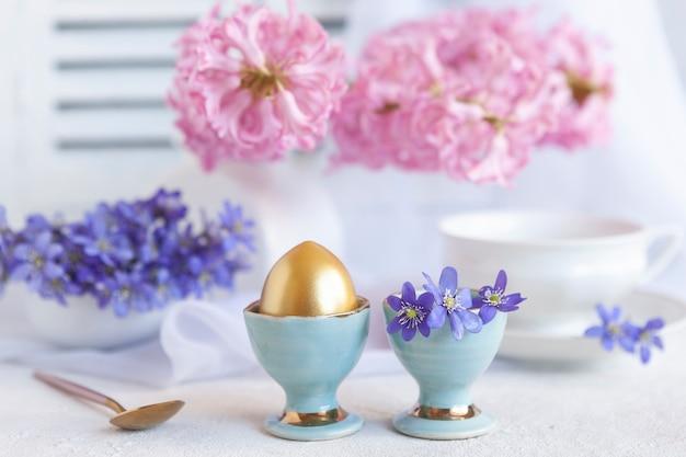 Свежий букет из нежных весенних цветов печеночника hepatica nobilis и золотого яйца в подставке для яиц