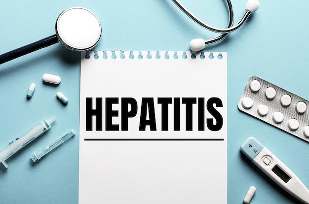 Гепатит, написанный на белом блокноте на синей поверхности возле стетоскопа, шприца, электронного термометра и таблеток. медицинская концепция