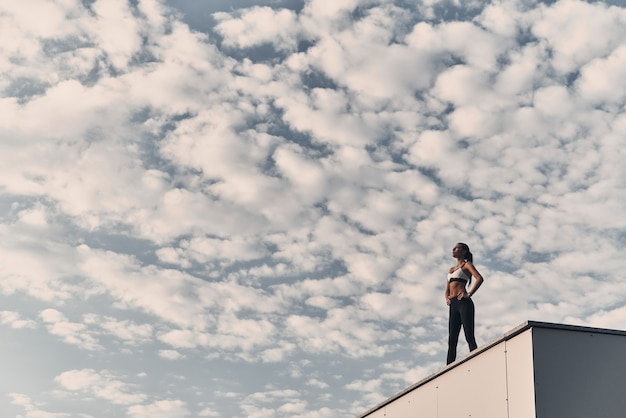 그녀의 몸은 휴식을 취했습니다. 야외에서 지붕에 서있는 동안 편안한 스포츠 의류에 현대 젊은 여성