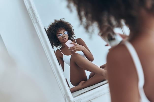 그녀의 몸매는 완벽하다. 집에서 바닥에 앉아있는 동안 거울에 셀카를 찍는 흰색 란제리에 아름다운 젊은 아프리카 여성의 반영