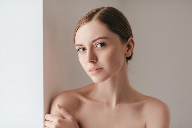Ее уверенность просвечивает. привлекательная молодая женщина с веснушками на лице смотрит в камеру и держит руку на плече