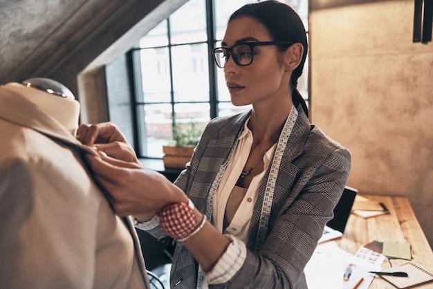Ее дизайн идеален. серьезная молодая женщина в очках регулирует воротник куртки на манекене, стоя в своей мастерской